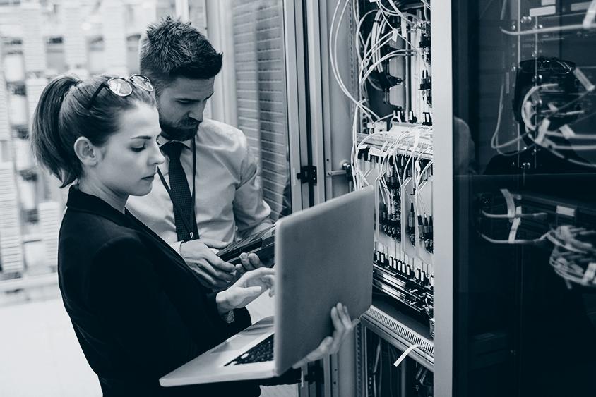 Mann og kvinne ser inn i skap med PLSer og styresystemer.