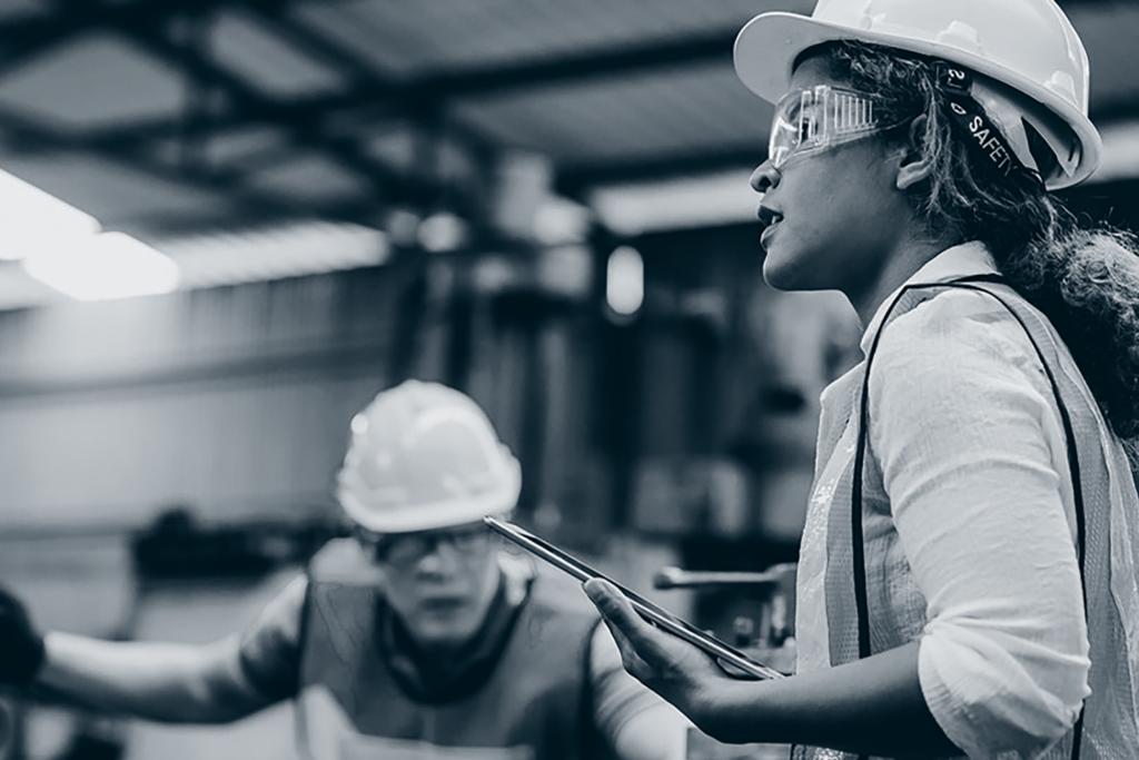 Kvinne og mann på gulvet i produksjonsfabrikk.