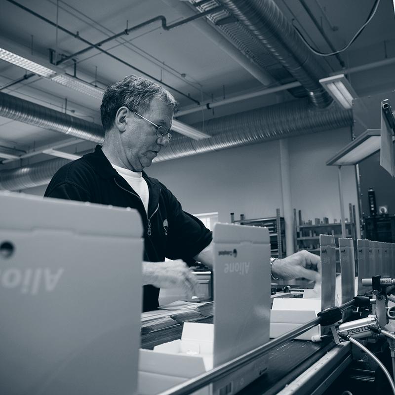 Bilde fra Coloplast: Mann står ved emballasjemaskin.