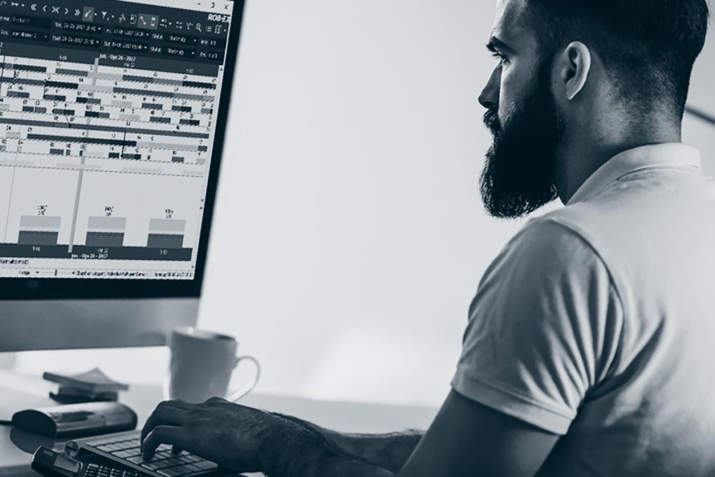 Mann sitter foran PC for produksjonsplanlegging.