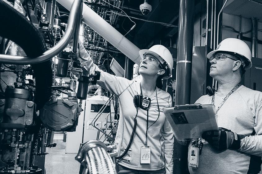 Kvinne og mann ser på vedlikehold i fabrikk.