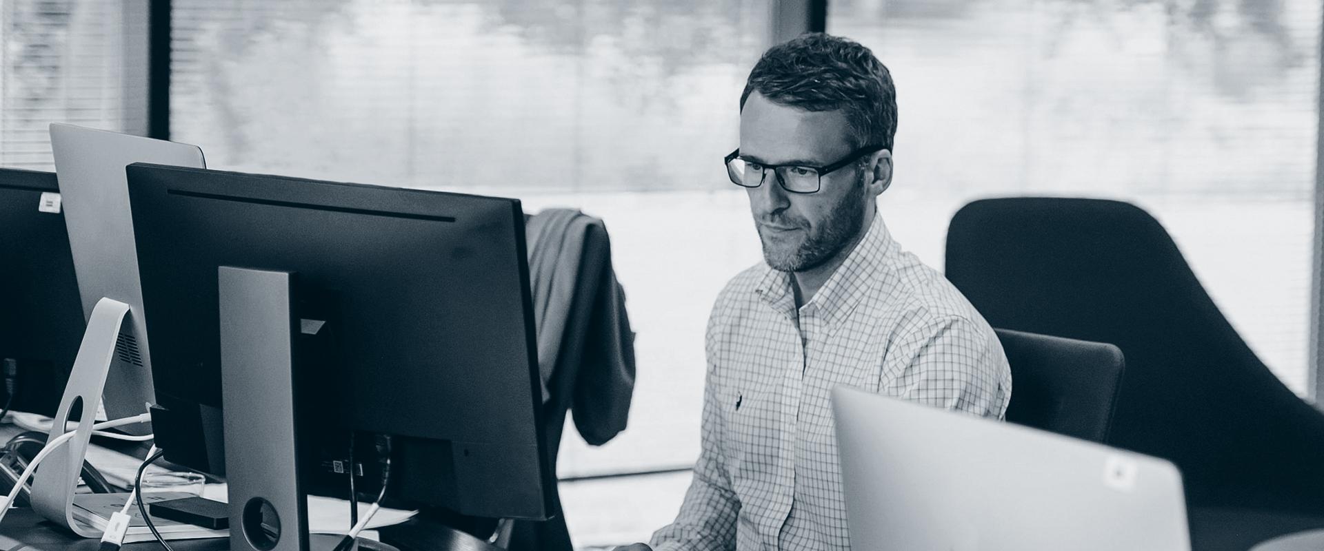 Konsentrert mann sitter foran PC.